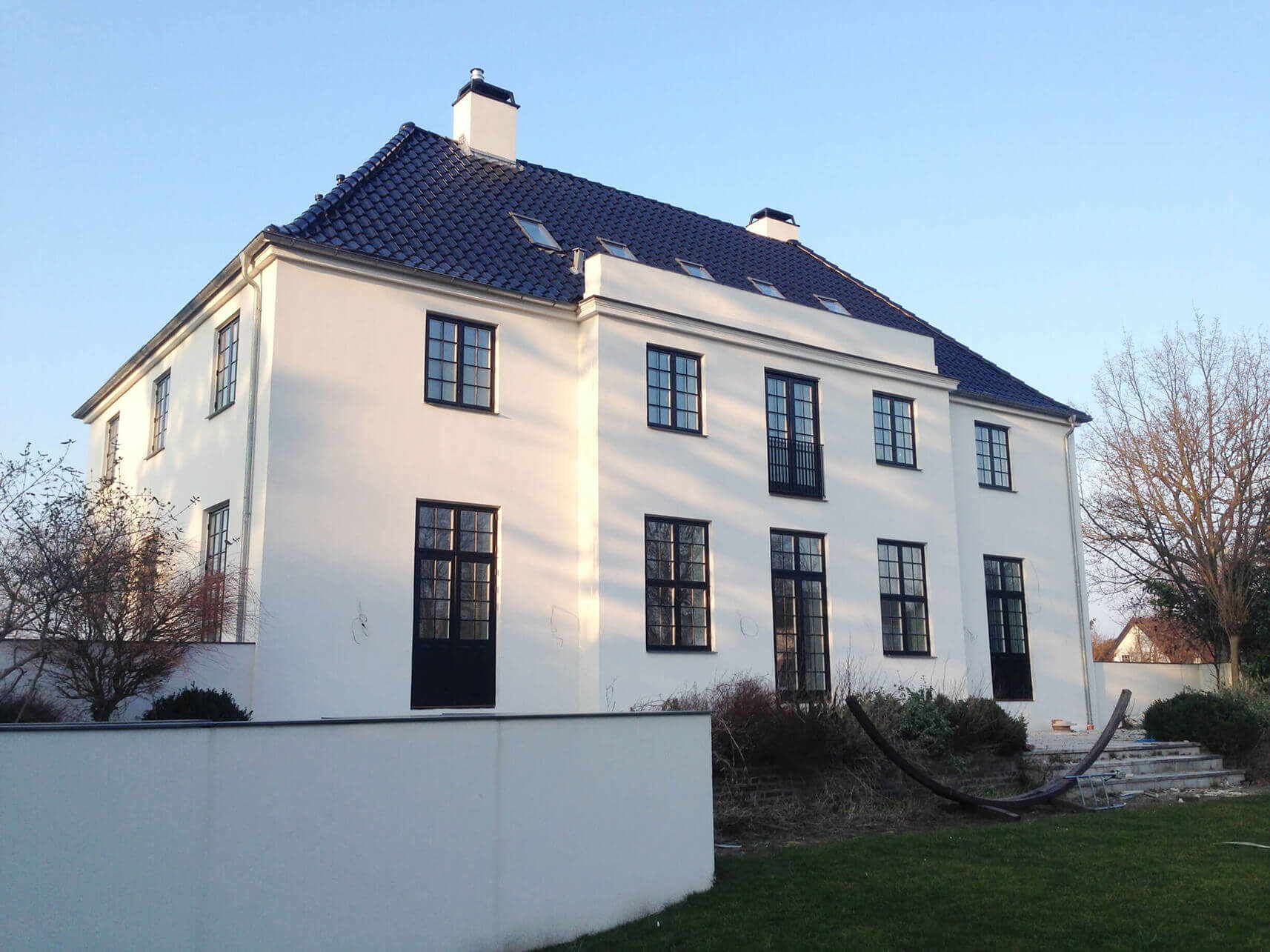 Stort hus med nypudset og isoleret hvid facade - Renoveret af Køge Bugt Facadeentreprise